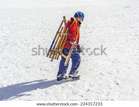 boy carries his sledge up the hill in winter - stock photo