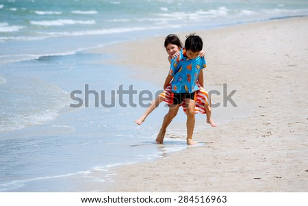 Boy carry his sister at his back on the white sand beach seaside - stock photo