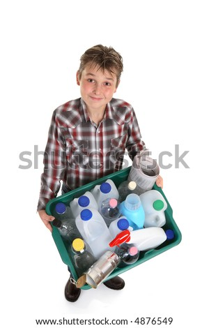 Boy carrying a recycling container full of empty bottles, cans, etc suitable for recycling. - stock photo