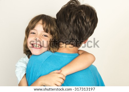 Boy carrying his sister smiling at home isolated on white background - stock photo
