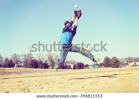 Boy catching a baseball, sandlot baseball, focus on shirt. - stock photo