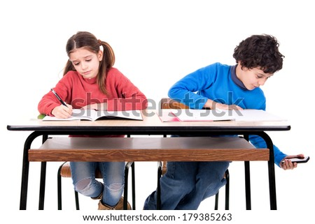Boy cheating with cellphone in the classroom - stock photo