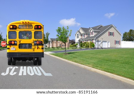 Boy Cheesy Smile Eyes Closed in Back Window of School Bus  on Crossing Sign on Street in Suburban Neighborhood - stock photo