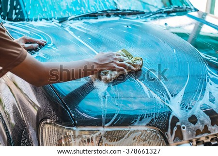 Boy cleaning car by foam from clean car care service. - stock photo