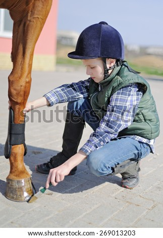 Boy cleans a hoof of horse - stock photo