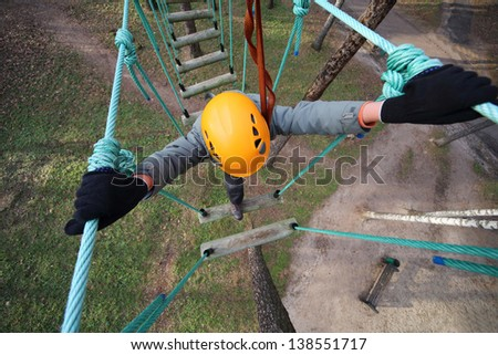 Boy climber walks on the rope bridge, the view from above - stock photo