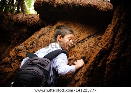 Boy climbing rock - stock photo