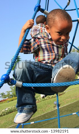 Boy Climbing Through Ropes - stock photo