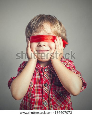 boy closed his eyes red ribbon - stock photo