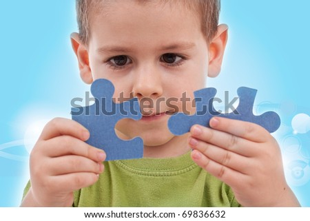 Boy connect puzzles - blue background - stock photo