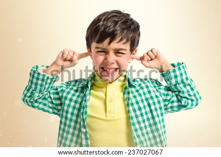 Boy covering his ears over ocher background.  - stock photo