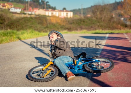 Boy crying and screaming in the street ground after falling off to his bicycle - stock photo