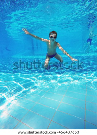 boy diving into a swimming pool - stock photo