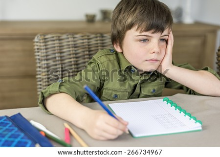 boy doesn't feel like making homework with hand under his head - stock photo