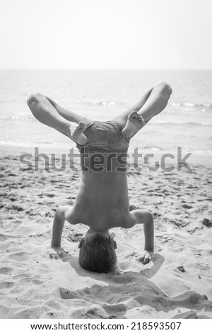 Boy Doing a Handstand on the beach. Black and white picture. - stock photo