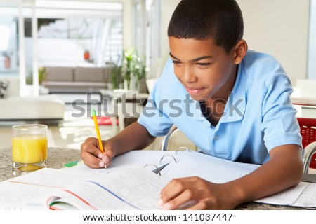 Boy Doing Homework In Kitchen - stock photo