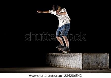 Boy doing skateboard trick on night - stock photo