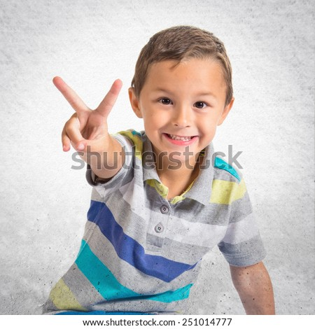 Boy doing victory gesture over textured background - stock photo
