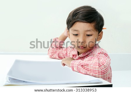 Boy drawing colored pencils in a book on room background. - stock photo