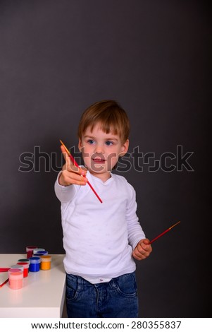 Boy draws with colored inks. In the studio on a gray background - stock photo