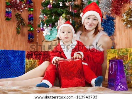 Boy dressed like Santa Claus with mother  celebrating Christmas in living room - stock photo