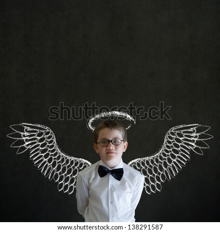 Boy dressed up as businessman, teacher, salesman or student with angel, halo, Christianity, religion, Jesus or investor wings on blackboard background - stock photo