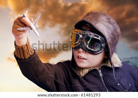 Boy dressed up in pilot outfit at sunset sky - stock photo