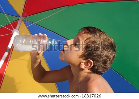 Boy drinking water under the colorful parasol - stock photo