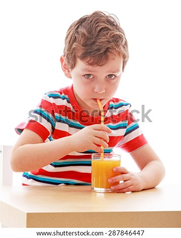 boy drinks from a glass of orange juice through a straw while sitting at table , close-up-isolated on white background - stock photo