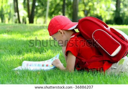 Boy during a school vacation has a rest in a wood reading the book - stock photo