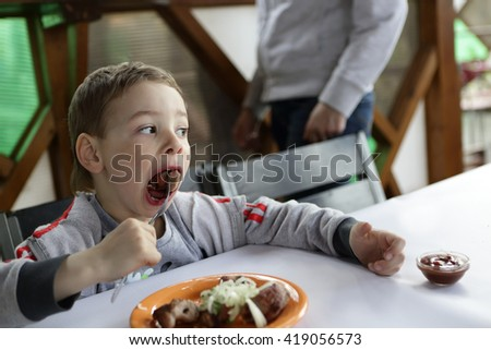 Boy eating kebab with onions in the cafe - stock photo