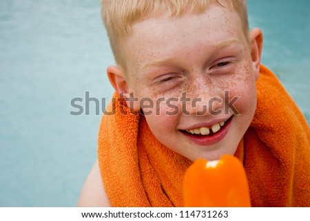 Boy eating orange popsicle by a swimming pool - stock photo