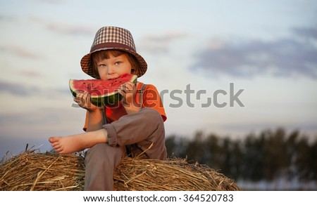 boy eating watermelon on a haystack - stock photo