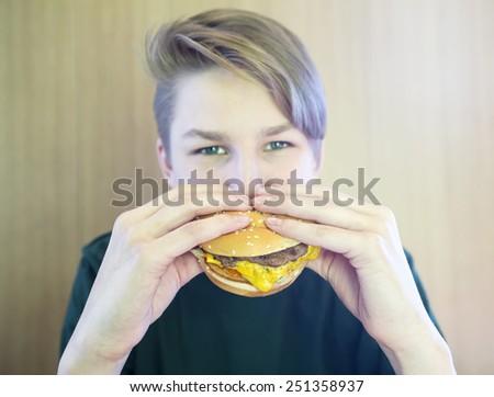 Boy eats a hamburger - stock photo