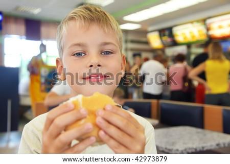 boy eats hamburger - stock photo