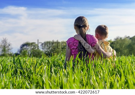 Boy embraced the girl sitting on the grass - stock photo