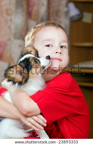 Boy embracing a puppy in his arms. - stock photo