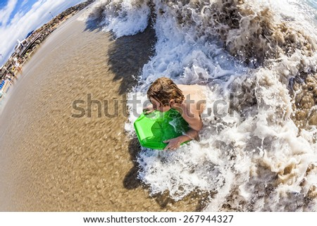 boy enjoys surfing in the waves in Lanzarote - stock photo
