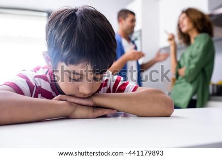 Boy feeling sad while his parents quarrelling in kitchen - stock photo