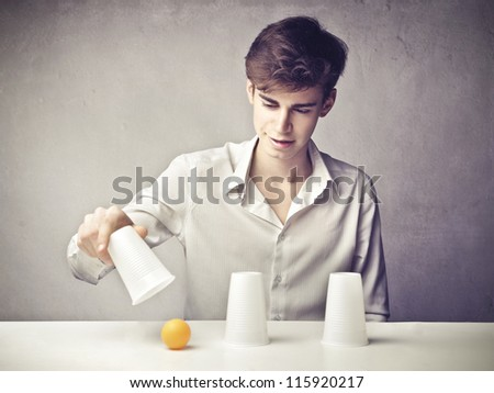 Boy finding a ball under a plastic glass - stock photo