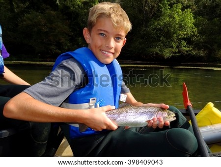 Boy fishing - child fishing from a canoe, proudly holding his catch (Rainbow Trout) - stock photo