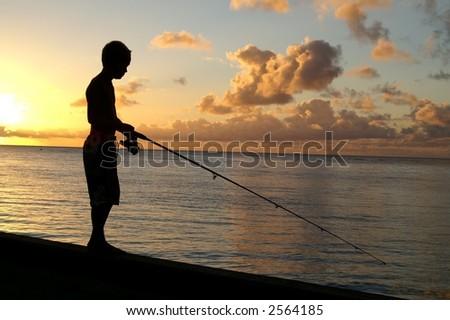 Boy fishing off pier - stock photo