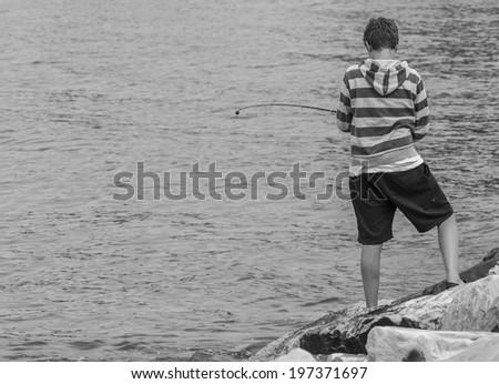 boy fishing on the coast - stock photo