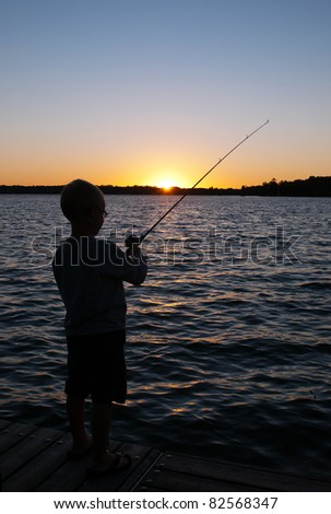 Boy Fishing Silhouette at Sunset on Lake - stock photo