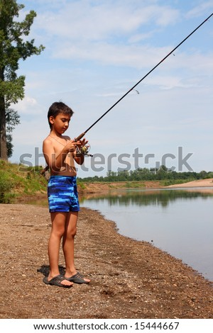 boy fishing with spinning on the river - stock photo