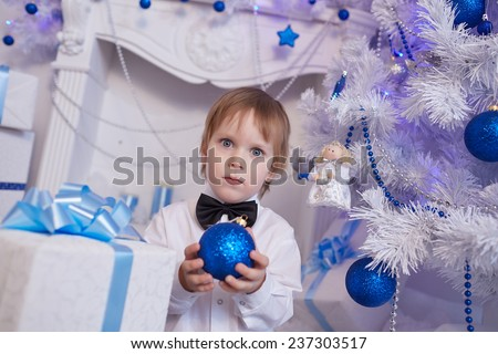 boy five years in anticipation of a gift, sitting near the Christmas tree, holding a blue balloon - stock photo