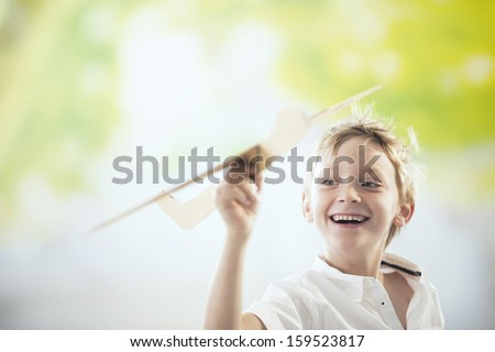 boy flying a wooden plane - stock photo