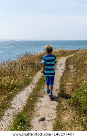 boy following a path towards the beach - stock photo