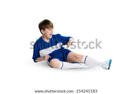 Boy football player in blue uniform against white background - stock photo