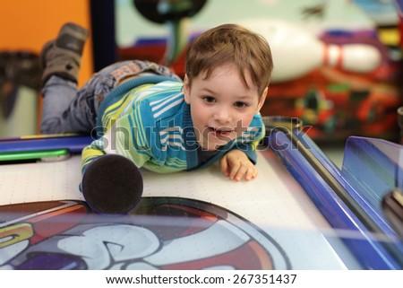 Boy gamble in air hockey at tha amusement park - stock photo